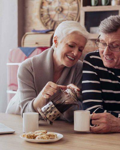 happy-senior-couple-drinking-tea-in-kitchen-2HT3SEC-edited